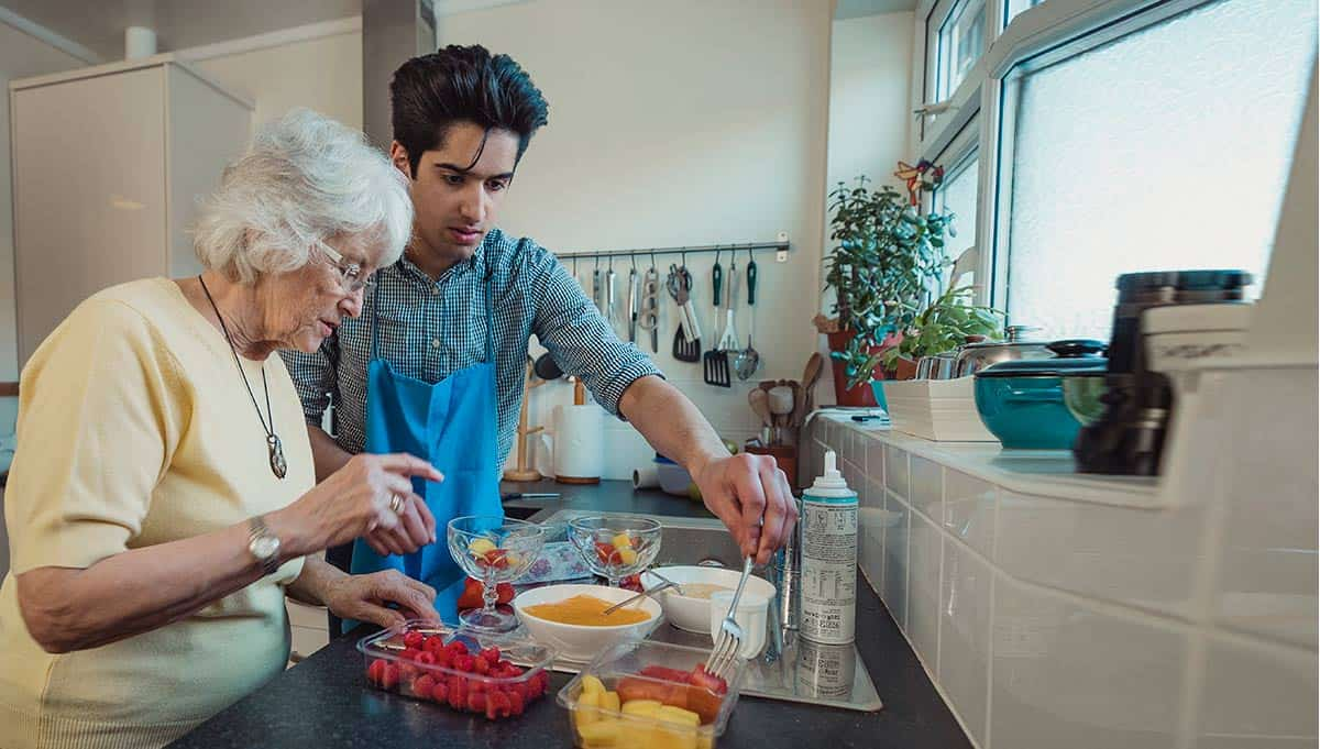 Volunteer cooking with person with Alzheimer's
